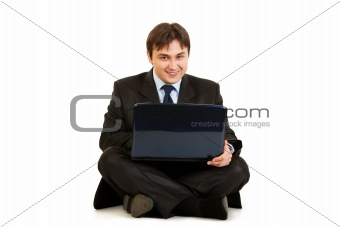 Smiling  businessman sitting on floor and working on laptop