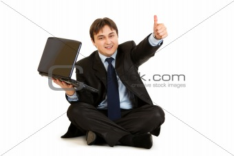 Smiling  businessman sitting on floor with laptop showing thumbs up gesture