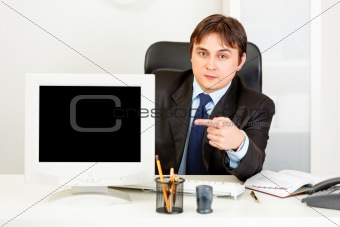 Authoritative businessman sitting at office desk and pointing finger at  monitor with blank screen