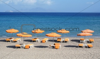 Greece. Kos island. Orange chairs and umbrellas on the beach