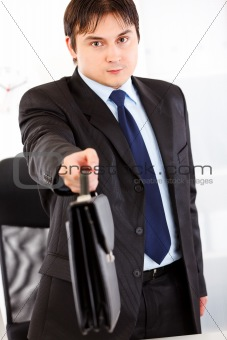 Authoritative businessman standing at office desk and giving briefcase. Close -up.