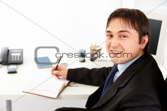 Smiling  businessman sitting at office desk and planning timetable in diary