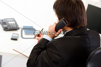 Businessman  in office talking on phone and making notes  in diary