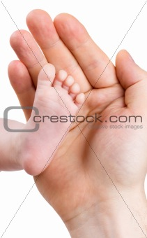 Small leg of the newborn baby girl in the big hand of the father, isolated on a white background