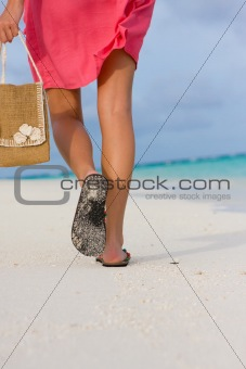 Young woman goes for a walk on a beach