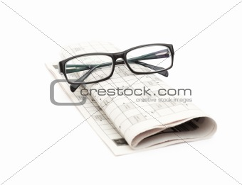 Reading glasses sitting on a newspaper