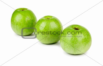 Three ripe and juicy green apples located in a line isolated on a white background