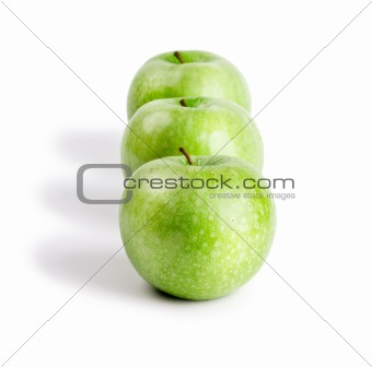 Three ripe and juicy green apples located in a line one after another isolated on a white background