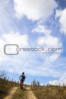 Young man riding mountain bike and watching cloudy sky