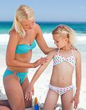 Mother applying sun cream on her daughter's back