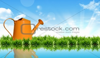 watering can on the grass with the bright sky.