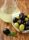 black and green olives and a bottle of olive oil on brown board