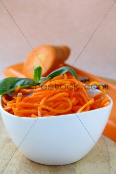 Carrot salad in white bowl  with basil