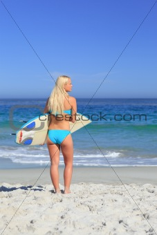 Beautiful blonde woman with her surfboard