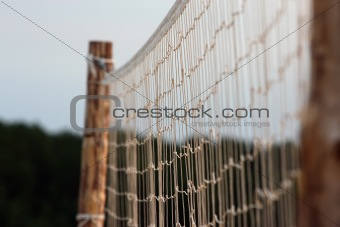 Beach volleyball net over blue sky and forest