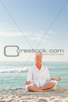 Mature woman practicing yoga on the beach