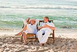 Elderly couple relaxing in their deck chairs