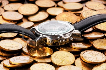 Time is money concept with watch and coins