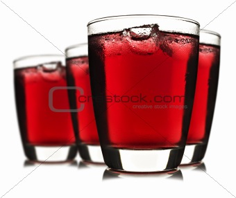 Four glasses of red fruit juice with ice