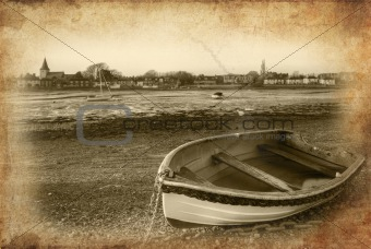 Old rowing boat in low tide harbour landscape at sunset with gru