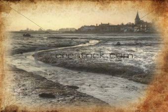 Low tide harbour at sunset with nearby town in distance retro gr