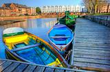Bright colorful rowing boats in urban canal landscape