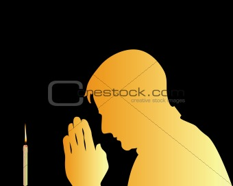 praying in front of a candle