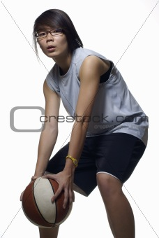 Asian teen female basketball player in defensive stance