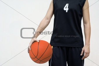 Asian teenage basketball player holding ball