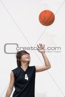 Asian female teen basketball player looking up at ball