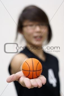 Asian teen holding tiny orange basketball in hand