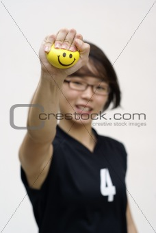 Asian female sporty lady squeezing yellow happy ball