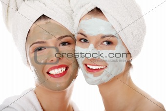 Young happy women with facial clay mask