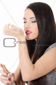 Beautiful woman applying perfume