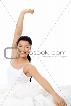 Happy young woman stretching in bed