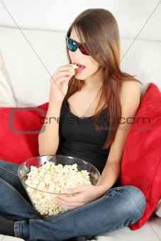 Beautiful young woman watching TV in 3d glasses