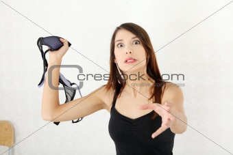 Angry woman with bra in hand.