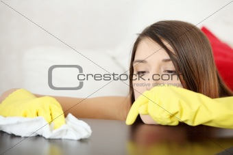 Tired young woman cleaning furniture table