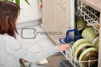 Young woman in kitchen doing housework.