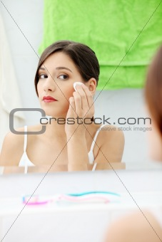 Young beautiful caucasian woman cleaning her face