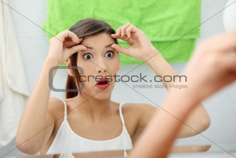 Shocked young woman checking her wrinkles