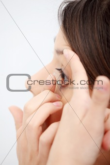 Woman putting a contact lens