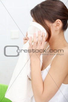 Beautiful woman wipes her face with a towel