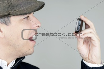 Man In Newsboy Hat Looks At Cell Phone In Amazement