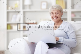 An elderly woman with a laptop
