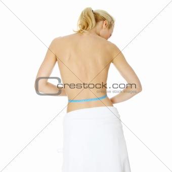Beautiful young caucasian woman measuring her body
