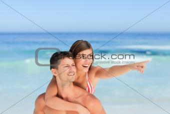 Handsome man having wife a piggyback on the beach