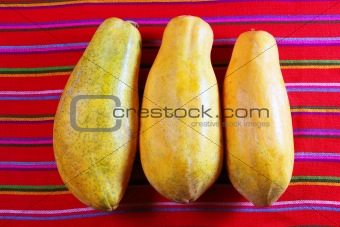 three papaya fruits on latin serape tablecloth