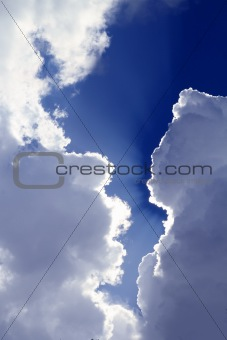 beams from sun in blue sky gray clouds skyscape