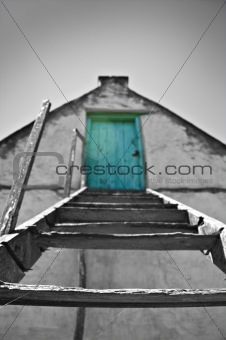 Green door in an old building with wooden stairs.